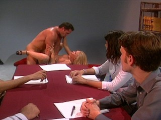 The blonde addresses the board, then undresses