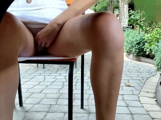 Alice in a street cafe upskirt pushed her panties and shows her pussy