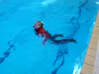 German girl with fully clothes swims in swimming pool