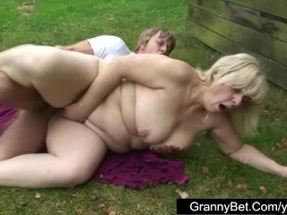 Old blonde is banged by young guy outdoors
