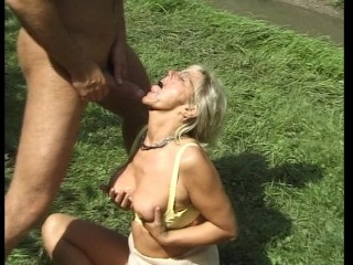Older lady younger man play around in the grass (clip)